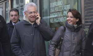 Italian premier Mario Monti takes a call on his mobile phone as he walks through a Milan street with his daughter Federica (right) 9 December 2012 after attending mass with his wife.