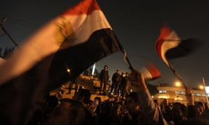 Egyptian army soldiers stand on top of a tank as opposition supporters and protesters wave national flags outside the presidential palace in Cairo.
