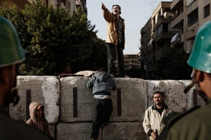 Egypt protests: Egyptians climb a concrete wall recently built near the presidential palace