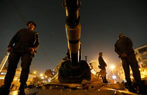 Egypt protests: Soldiers stand guard on top a tank in front of the presidential palace