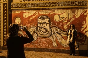 Egypt protests: A woman has her photo taken in front of graffiti portraying president Morsi