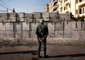 Egypt protests: A soldier stands guard in front of the presidential palace