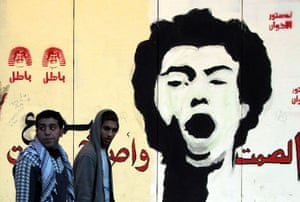 Egypt protests: Anti-Morsi protesters walk in front of a mural of activist Gaber Salah