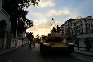 Egypt protests: Egyptian army soldiers sit on top of their tank as the sun sets in the city