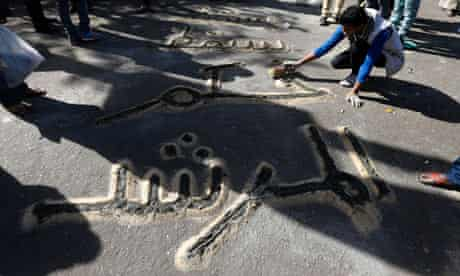 A man writes a message using sand in the street near Tahrir Square