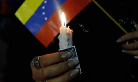A supporter of Hugo Chávez holds a candle