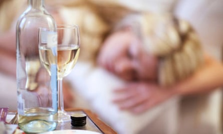 Bottle of wine and young woman asleep