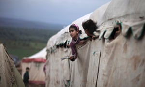 Syrian girls who fled their homes with their families peek out of their makeshift school at a camp for displaced Syrians in the village of Atmeh, Syria. This tent camp sheltering some of the hundreds of thousands of Syrians uprooted by the country's brutal civil war.