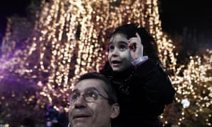 A young girl at the lighting of the Christmas tree at the main Syntagma square in Athens last night. It will cost 90% less than in recent years.