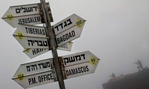 Signpost on Golan Heights in front of cutouts of soldiers