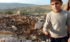 A Syrian boy at the site of crater where residents said a Scud missile landed near the military base of Sheikh Suleiman on the outskirts of the northwestern town of Darret Ezza. A former Syrian officer who served in a battalion specialising in surface-to-surface missiles told AFP that regime forces had fired Scuds three days ago, but the government has denied this.