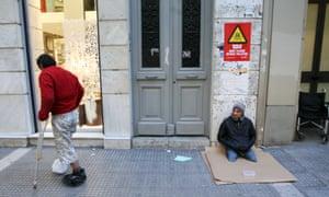 Two beggars wait on a sidewalk in Thessaloniki on December 13, 2012.