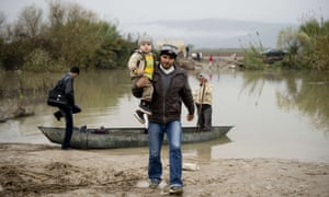 A Syrian man from Jisr al-Shughur carries his son as a family gets ready to board a boat to flee across the Orontes river to Turkey near the northern Syrian town of Darkush.
