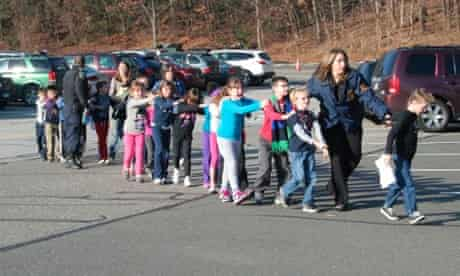In this photo provided by the Newtown Bee, Connecticut state police lead children from the Sandy Hook elementary school.