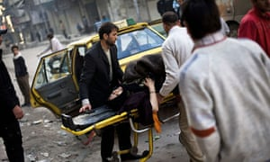 A woman injured by Syrian army shelling lies on a hospital trolley in a rebel-held area of Aleppo