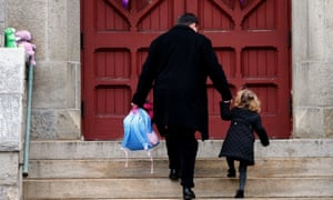 A man helps a young girl up the stairs as they arrive for services at Trinity Church in Newtown.