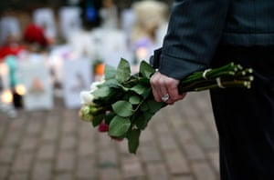 Sandy Hook: A woman clutches a bouquet of roses as she stands at a makeshift memorial