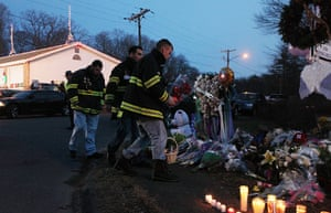 Sandy Hook: Firefighters pay their respects at a makeshift memorial near the school