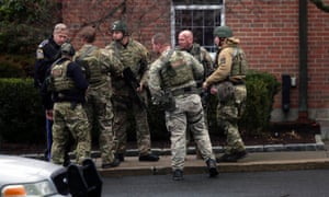 A Swat team prepares to enter St Rose of Lima Roman Catholic Church in Newtown