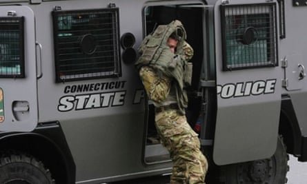 A Connecticut state police officer puts on his vest next to his armored vehicle outside St Rose of Lima Roman Catholic Church in Newtown, Connecticut.