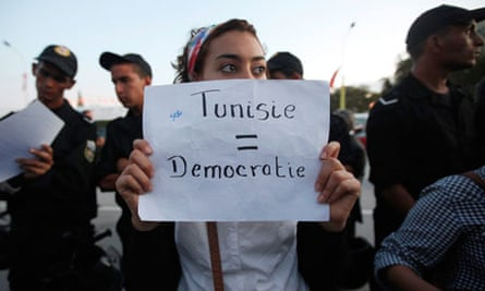 A Tunisian demonstrator holds a sign during a protest against the Islamist Ennahda movement in Tunis