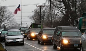 A hearse and family limousines for six-year-old shooting victim Jack Pinto rolls past a flag at half staff as the funeral procession heads through the historic district in Newtown, Conn., Monday, Dec. 17, 2012.