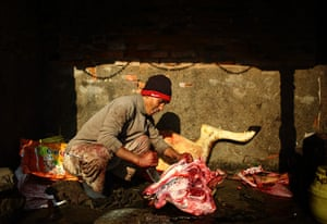24 hours in pictures: A butcher slices meat from the head of a buffalo