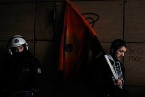 24 hours in pictures: An employee from Hellenic PostBank holds a flag next to a riot policeman