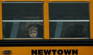 A child looks out of a bus window as it passes by Saint Rose of Lima Church where the funeral of James Mattioli, 6 is taking place in Newtown, Connecticut. Most children in Newtown returned to classes for the first time since last week's massacre, but survivors of the shooting stayed at home and their school remained a crime scene.