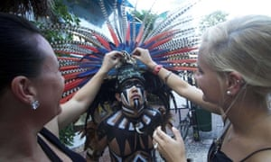 German tourists interact with a Mexican man wearing a pre-hispanic costume at a tourist area of Playa del Carmen in Quintana Roo state, Mexico, during preparations for the celebration of the end of the Maya Long Count Calendar, Baktun 13, and the beginnig of a new era.