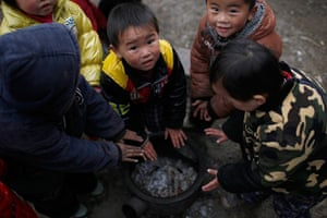 FTA: Aly Song: Children warm their hands over a fire