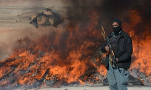 An Afghan policeman standing guard as a pile of narcotics is burned by officials on the outskirts of Jalalabad Nangarhar province.