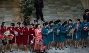 Staff members at a hotel in Pyongyang, wait to welcome scientists and technicians from the recent successful launch of a North Korean rocket that sent an artificial satellite into orbit