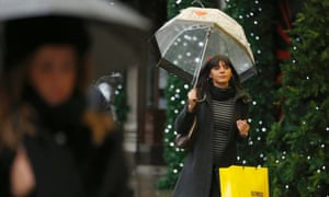 Christmas shoppers walk along Oxford Street in a wet central London.
