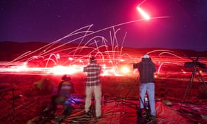 In this long exposure image visitors to the Big Sandy Machine Gun Shoot firing their weapons as flares and tracer fire light up the night sky outside Wikieup, Arizona.