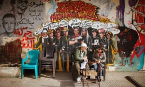 People sit against a wall filled with graffiti at Tahrir Square in Cairo as protests continue in the square.