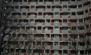 A person looks out from a balcony on a tower block in east London, UK.