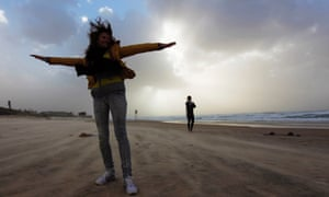 A woman raises her arms on a windy day at the beach in the southern Israeli city of Ashkelon. Winds reached speeds of up to 35 knots along the coast.