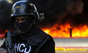 A police officer stands guard while confiscated drugs burn in the background inside a military base in Santo Domingo, Dominican Republic.