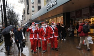Men walk along dressed as Father Christmas as shoppers brave the rain to shop on Oxford Street, London. Fears that consumers are reining in their spending ahead of Christmas were fuelled today after it emerged that sales volumes failed to rebound last month  A predicted return to growth did not materialise, with official figures from the Office for National Statistics revealing flat sales volumes between October and November.