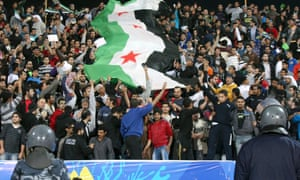 Fans of Syria hold the flag of the Syrian opposition during their West Asian Football Federation (WAFF) Championship final soccer match against Iraq in Kuwait City December 20, 2012.
