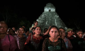 Poverty-stricken Mayan activists stand before temple ruins to draw attention to their plight.