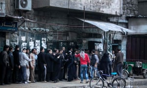 Syrian residents stand in line outside a bakery during heavy fighting between Free Syrian Army fighters and government forces, unseen, in Aleppo, Syria.