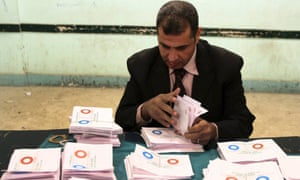 """An official counts """"agree"""" ballots after polls closed in Bani Sweif.  Early indications showed Egyptians approved an Islamist-drafted constitution after Saturday's final round of voting in a referendum despite opposition criticism of the measure as divisive."""