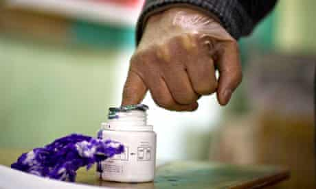 A Egyptian voter marks his finger with indelible ink to prove that he cas