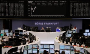 Traders are pictured at their desks in front of the DAX board at the Frankfurt stock exchange December 27, 2012.