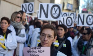 """A public health worker holds up a sign reading, """"With less staff, worse quality"""" during a protest outside a public health office against cuts in the service, in Madrid, Thursday, Dec. 27, 2012."""