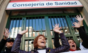 Demonstrators shout slogans during a protest against the local government's plans to cut spending on public health care, outside Madrid's health regional office in Madrid December 27, 2012.