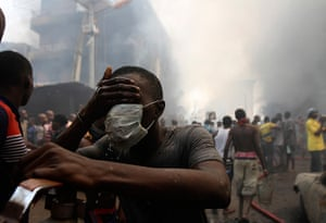 24 hours in pictures: A volunteer cleans his face near the site of a fire, Nigeria