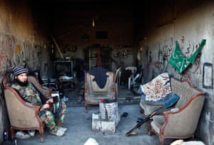 24 hours in pictures: A Free Syrian Army fighter sits in a garage